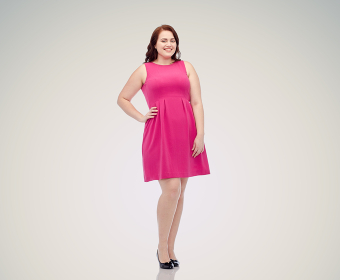 happy young plus size woman posing in pink dress