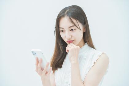 嫌な感情でスマートフォンを見る女性