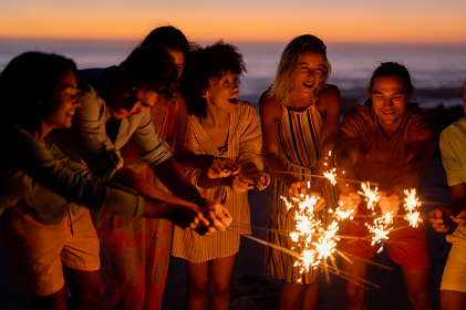 A multi-ethnic group of friends enjoying their time together on a beach during sunset, standing in a circle, holding sparklers and laughing