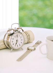 目覚まし時計と新聞とコーヒー