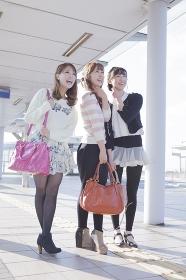 友達と遠くを見つめるバッグを持つ笑顔の女性