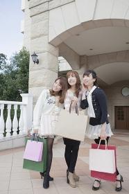 友達と笑顔でショッピングバッグを持つ女性