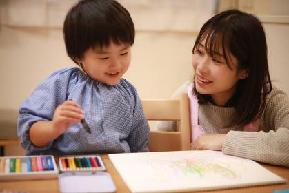 お絵描きする男の子と保育士イメージ