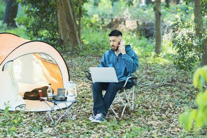 キャンプをしながら仕事をする男性