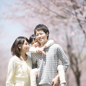 桜の前でおんぶをする親子