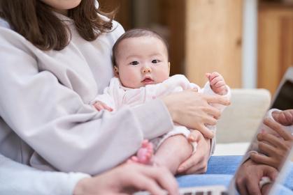 ママに抱っこされるカメラ目線のアジア人の赤ちゃん