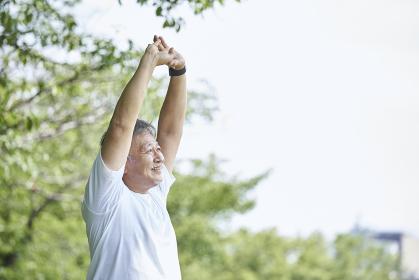 屋外でストレッチをするシニアの男性