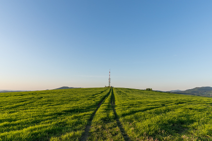 View of a broadcasting tower lying on a hill in the middle of a landscape in a field on a hill. , Czechia, Zlin Region, Valasske Mezirici