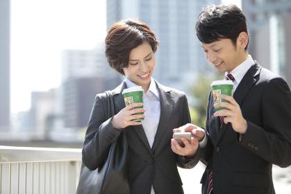 スマートフォンを見るビジネスマンとビジネスウーマン