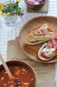 キッチンの白いタイルの上に置かれた朝食風のミネストローネスープのセット