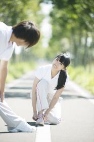 靴紐を結び直す女性と準備運動をする男性
