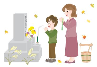 秋のお彼岸にお墓参りをする母と息子