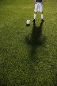腰に手を当てるサッカー選手とボール