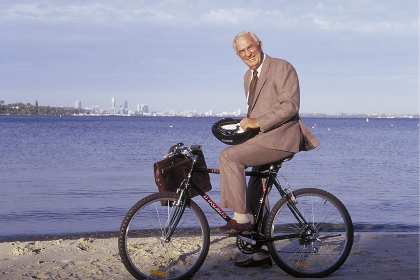Portrait, Outdoor, Ganzfigur, weisshaariger Senior bekleidet mit Anzug und Krawatte, ca. 70 Jahre alt, mit dem Fahhrad am Strand