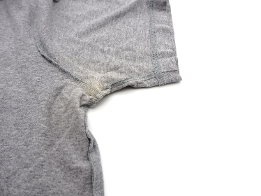 Yellow stain under armpit on T-shirt isolated on white background.