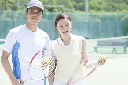 テニスコートで微笑む男女