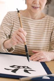 書道をするシニア女性の手元