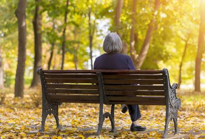 Elderly woman sitting on a bench in autumn park