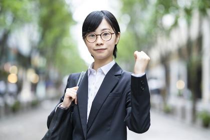 ガッツポーズをするスーツ姿の若い女性