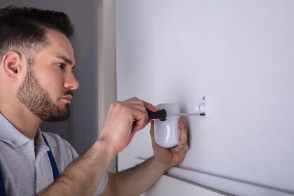 Electrician Installing Security System Door Sensor On Wall