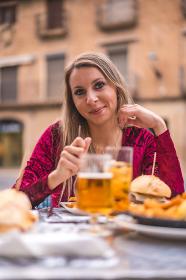 Portrait of pretty girl eating in red dress , Olite, Navarre, Spain