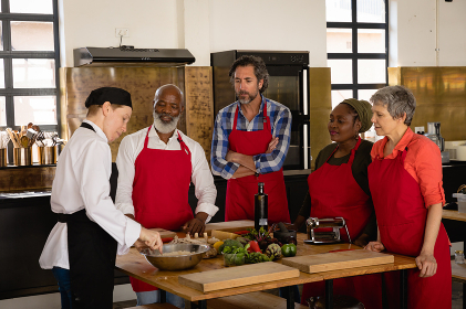 Side view of a multi-ethnic group of Senior adults at a cookery class, the diverse adult students listening to instructions from a Caucasian female chef wearing chefs whites and a black hat and apron, standing around a wooden table of ingredients