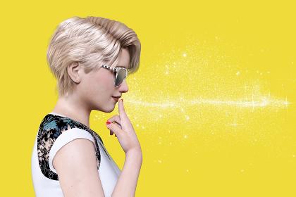 サングラスをかけた金髪のショートヘアの女性が横を向いて人差し指を口元に添えているポーズ
