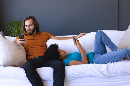 Happy diverse couple sitting on sofa embracing and using smartphones. staying at home in isolation during quarantine lockdown.