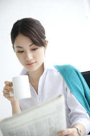新聞を読みながらくつろぐビジネスウーマン