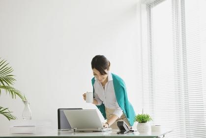 ノートパソコンに向かう笑顔のビジネスウーマン