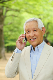 新緑と電話をするシニアの日本人男性