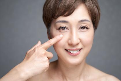 目元を押さえる中年の日本人女性