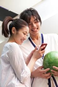 スマートフォンを持つ女性と微笑む男性