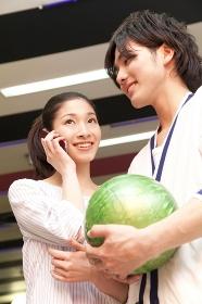 電話する女性とボウリング球を持つ男性