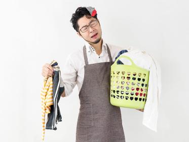 溜まった洗濯物に困る男性のイメージ