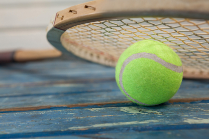 Close up of wooden tennis racket leaning on fluorescent yellow ball