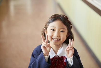 ピースサインをする幼稚園児の女の子