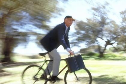Outdoor, Ganzfigur, ca. 60 Jahre alter Mann, bekleidet mit blauer Anzugsjacke, heller Hose und Baseballkappe mit Aktentasche unterwegs mit dem Fahrrad