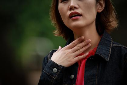 喉に違和感を感じる女性