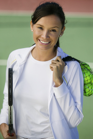 Woman with tennis balls and racket standing on tennis court portrait