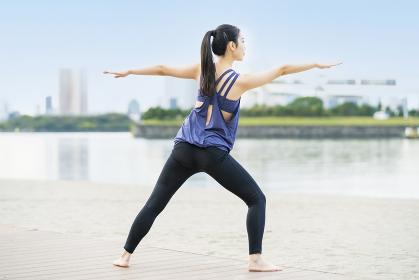 都市のビーチでヨガをする若い女性