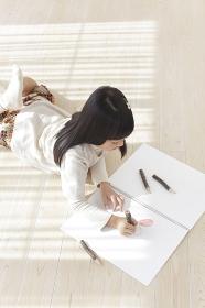 スケッチブックに色鉛筆で絵を描く女の子