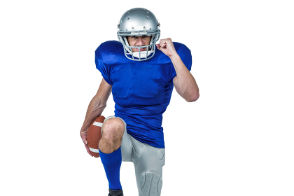 American football player standing on one leg while holding ball