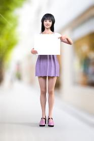 笑顔のロングヘアの黒髪の女の子が白いメッセージがかけそうなフリップを指差しながら持っている