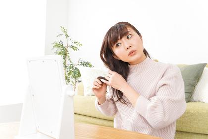 髪の毛のケアをする若い女性
