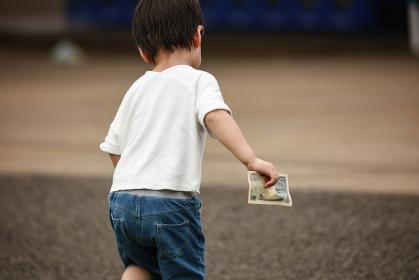 お金を手に持ち走り出す男の子