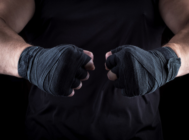 two men's hands wrapped in a black bandage
