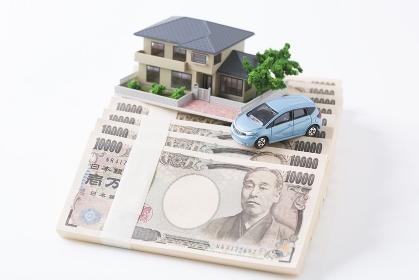札束の上に置かれた家と車の模型