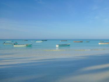 タンザニア・ザンジバル島の遠浅ビーチと白い砂浜と複数の船