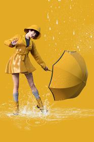 雨上がりのなか黄色い傘のしずくを落とす黄色いレインコートを着た女性